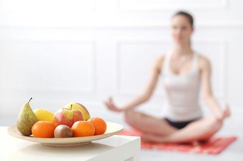 Chica en postura de yoga con comida sana